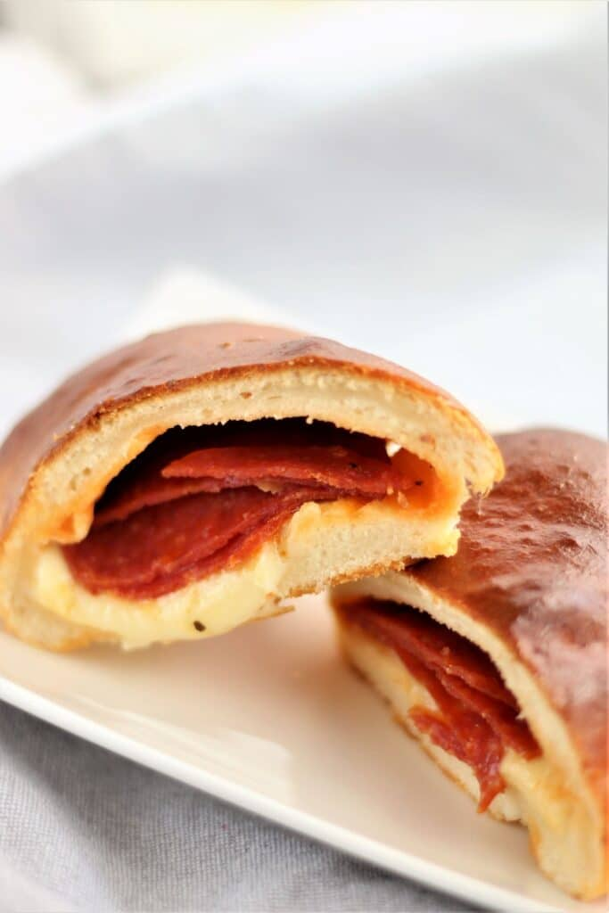 pepperoni bread cut open at a diagonal and placed on white plate