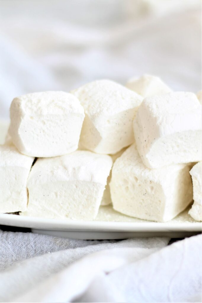 marshmallows stacked on white plate over white towel